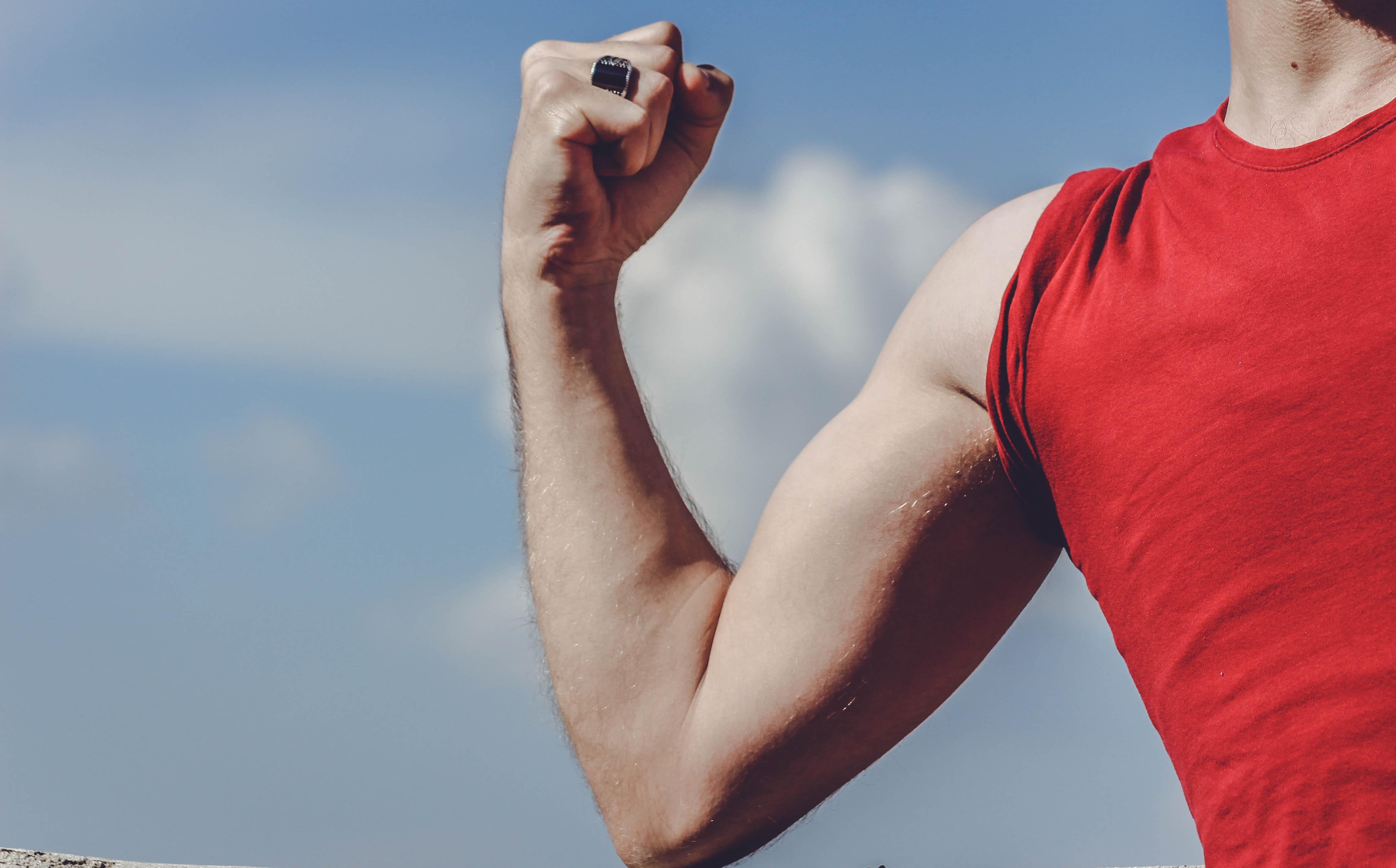 man-raising-his-right-arm-2080544